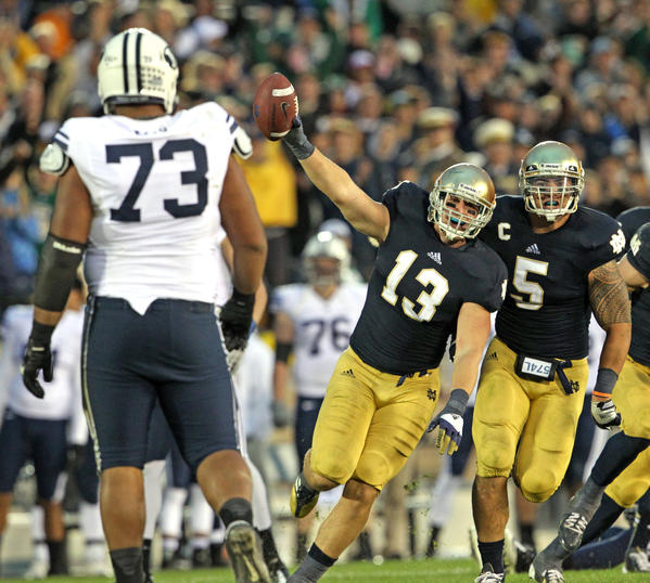 Notre Dame Fighting Irish linebacker Danny Spond (13) celebrates his interception with a handful of seconds left on the clock while Brigham Young Cougars offensive linesman Solomone Kafu (73) walks away at Notre Dame Stadium, in South Bend, Indiana, on Saturday, October 20, 2012. On the right is Notre Dame Fighting Irish linebacker Manti Te'o (5).