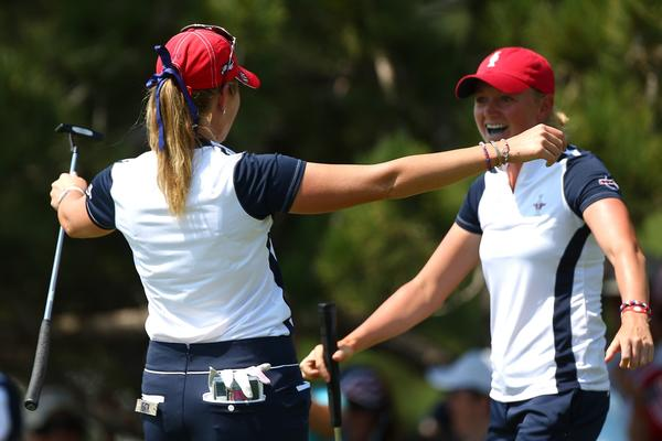 Stacy Lewis (R) and Paula Creamer react after winning their match by one hole on the 18th green.