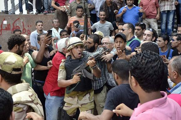 An Egyptian soldier points his weapon as he helps an Islamist man leave Cairo's Al Fatih mosque, where protesters had been surrounded by security forces and vigilante groups. The standoff ended Saturday after religious leaders intervened.