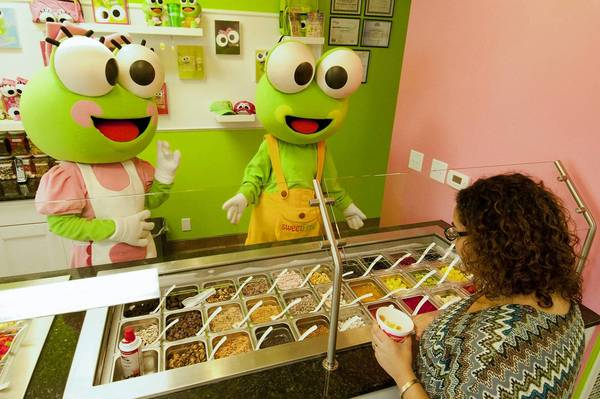 """Cookie"" and ""Scoop"" help JoAnn Almocherki of Allentown decide on toppings for her frozen yogurt at the newly opened sweetFrog in the Village West Shopping Center in Allentown."