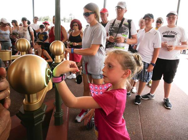 Madison Laughman, 7, with her mother (background) Nicole Laughman, holds up a wristband to check in using the new MyMagic  turnstiles, at Main Street USA at the Magic Kingdom, Walt Disney World, Thursday, August 15, 2013. (Joe Burbank, Orlando Sentinel)
