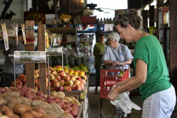 Dean and Don's is a family owned farmers' market that has been open seasonally on Warwick Blvd for many years. Karen Ridlow, foreground, opens a bag while June Tharpe, background, wheels a cart through the store.