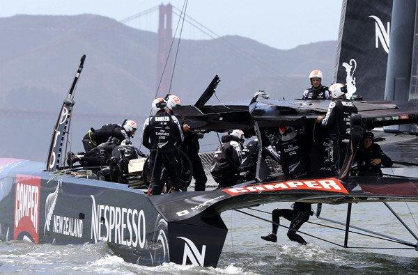 Emirates Team New Zealand crew members make repairs to their damaged catamaran following the first race of their America's Cup challenger series final on Saturday in San Francisco Bay.