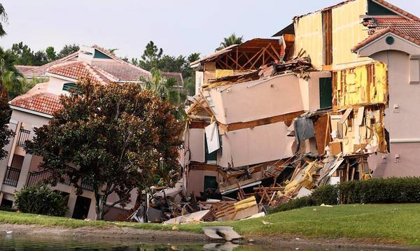Buildings collapse into a sinkhole at the Summer Bay Resort on U.S. Highway 192 in Clermont, Florida, Monday, August 12, 2013. Guests had only 10 to 15 minutes to escape the collapsing buildings at the Summer Bay Resort on U.S. Highway 192 in the Four Corners area, located about 7 miles east of Walt Disney World resort, where a large sinkhole- about 60 feet in diameter and 15 feet deep- opened in the earth late Sunday. (Red Huber/Orlando Sentinel/MCT) ORG XMIT: 1141973 ** HOY OUT, TCN OUT **
