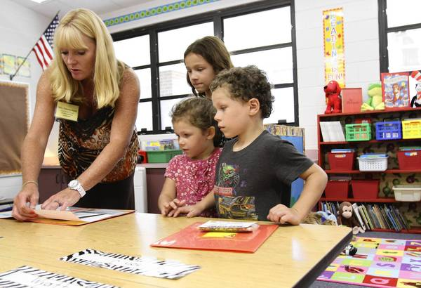 "Kindergarten teacher Tammy Keen shows where student Alexander Beach, 5, will be sitting , as his sisters Savannah, 7, left, and Sierra, 3, look on, during Seminole Springs Elementary's ""Meet the Teacher"" event on Thursday, August 15, 2013. . (Tom Benitez/Orlando Sentinel)"