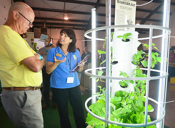 Jennifer Lerche, right, qualifying national marketing director for Juice Plus shows William Benson of Princess Anne, Md., the Tower Garden by Juice Plus Saturday at the first Mid-Atlantic Emergency Preparedness and Survival Expo at the Washington County Agricultural Education Center in Hagerstown.