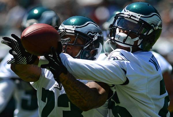 Eagles defensive backs Patrick Chung (23) and Cary Williams both reach for the ball during a drill Monday at Lincoln Financial Field.