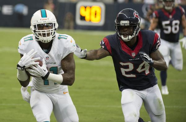 Mike Wallace (11) of the Miami Dolphins pulls in a pass in front of Johnathan Joseph (24) of the Houston Texans in the first half of their preseason game on Saturday, August 17, 2013, in New Orleans, Louisiana. (George Bridges/MCT)
