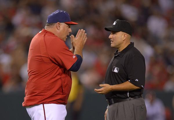Angels Manager Mike Scioscia pleads his case with second base umpire Eric Cooper after Houston Astros' L.J. Hoes was called safe at second during the ninth inning. The call was eventually reversed.