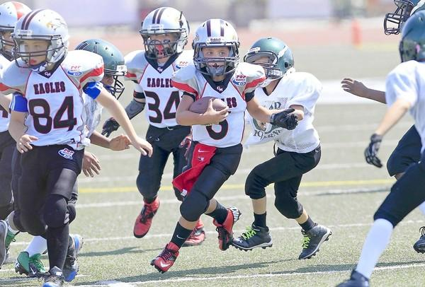 J.R. Mendez, center, carries the ball for the Costa Mesa Pop Warner Eagles of the Mighty Mites Division during a scrimmage against Upland at Jim Scott Stadium on Saturday.