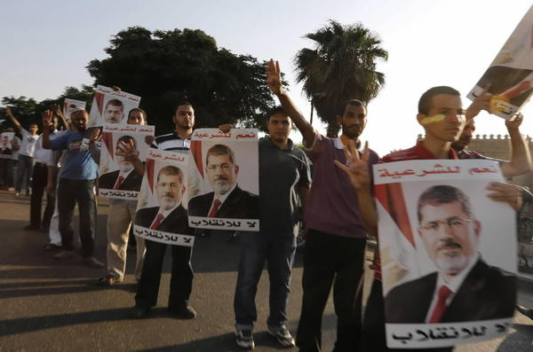 Supporters of deposed Egyptian President Mohamed Mursi hold up posters of him during a protest along Zahara street in Cairo.