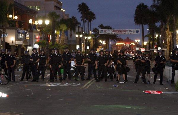 A large police presence moves rioters away from Main Street in Huntington Beach following a surfing contest on July 28.