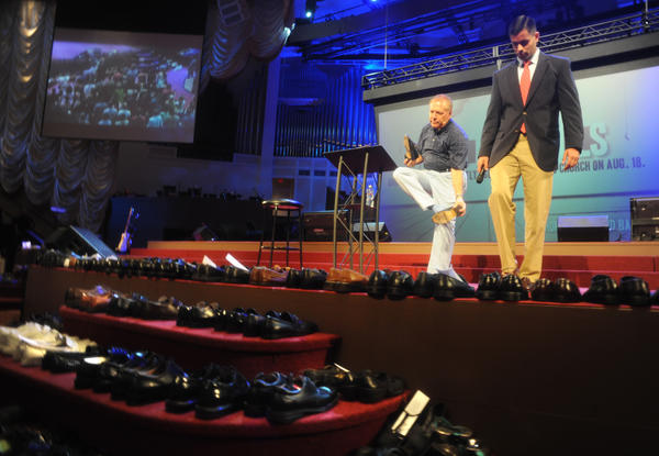 "Pastor Larry Thompson, left, and Minister Jeff Creiver of the First Baptist Church in Ft. Lauderdale remove their shoes during a ""Soles of Soles,"" service."