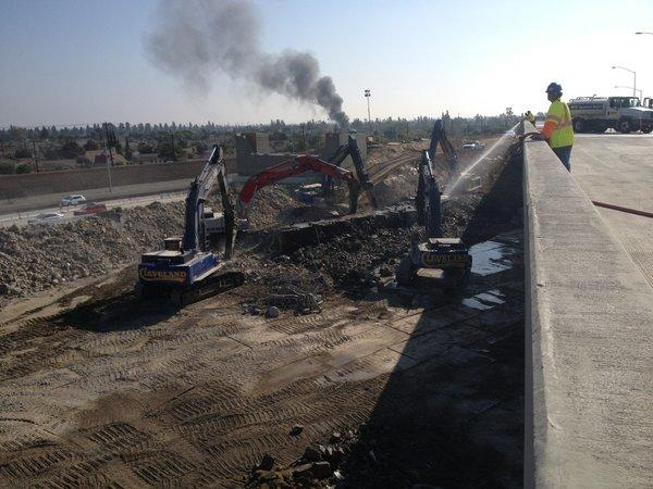 Demolition crews work on bridge removal project on 405 Freeway in Orange County.