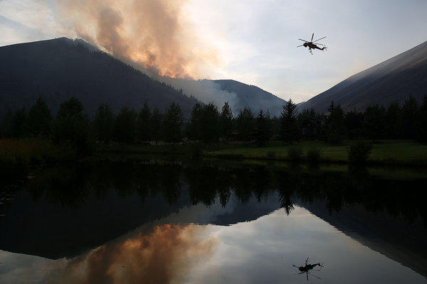 A helicopter descends Saturday to refill with water from a pond while battling the Beaver Creek fire in Idaho.