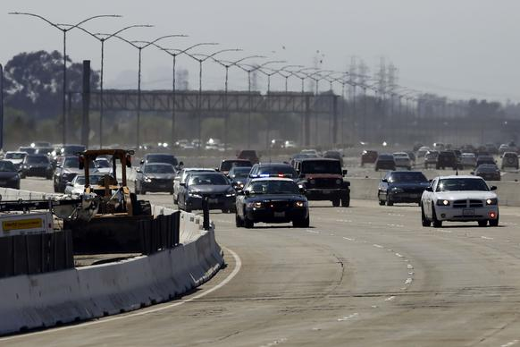 Police cars lead the way as the 405 Freeway in Orange County reopens.