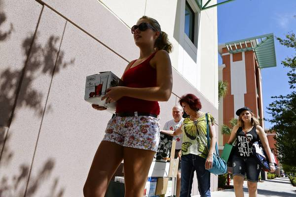 Shannon Fagan, 18, walks with her belongings as she and her family, dad Pat, mom Patti and twin sister Kaitlyn, help out. Shannon was moving into her new student housing at UCF on campus Thursday morning.