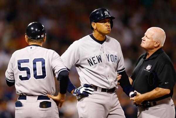 Alex Rodriguez is tended to by a trainer at first base after being hit by a pitch in the 2nd inning against the Red Sox.