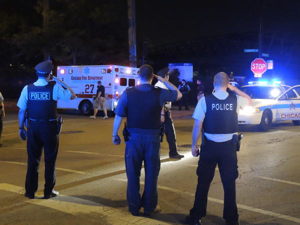 Officers salute an ambulance carrying the body of a Chicago Police Department sergeant who died while off-duty Sunday.