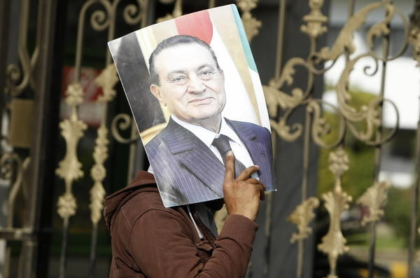 A supporter of Egypt's deposed president Hosni Mubarak holds up his picture outside the Maadi Armed Forces hospital.