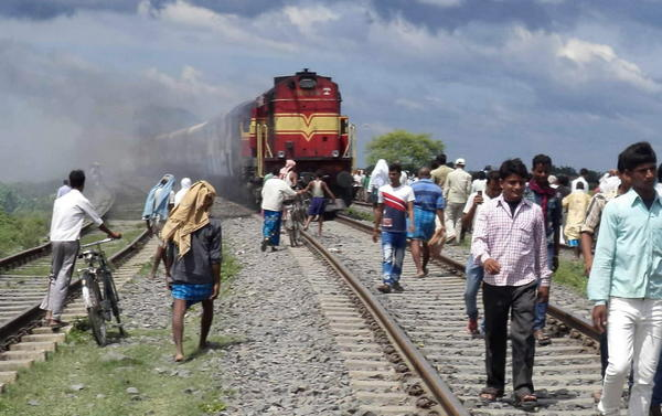 Indians walk on railroad tracks as train coaches of the Rajya Rani Express, set on fire by an angry mob, burn after the train plowed into a crowd of Hindu pilgrims at the Dhamara Ghat railway station.