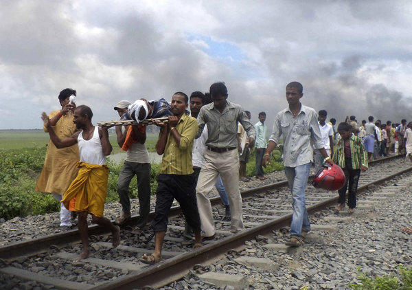 Indian villagers carry an injured person along a rail track after a train ran over a into a crowd in Dhamara Ghat.