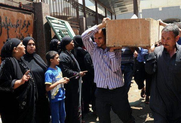 Egyptians at a Cairo morgue Monday carry the coffin of one of more than 35 Muslim Brotherhood prisoners killed the previous day.