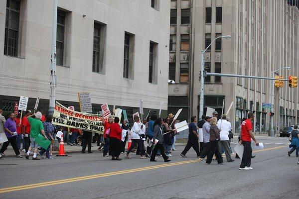 Protesters cross the street in front of federal court in Detroit on Aug. 2.
