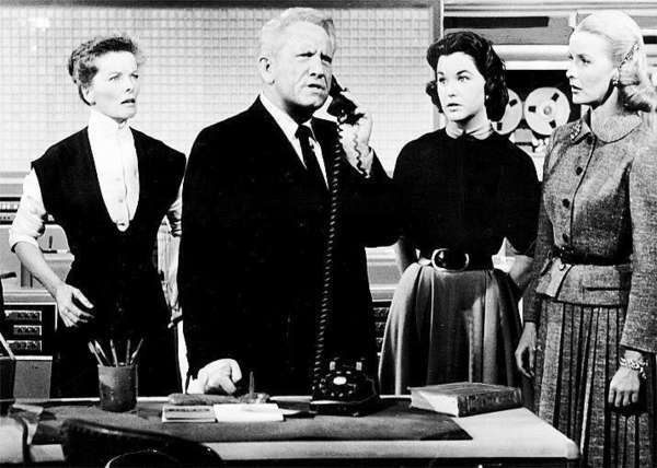 "Katharine Hepburn and Spencer Tracy star in the 1957 comedy ""Desk Set,"" which revolves around computerizing a research library. The EMARAC computer is seen in the background."
