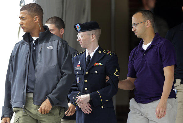 Army Pfc. Bradley Manning, center, is escorted to a security vehicle outside a courthouse in Fort Meade, Md.