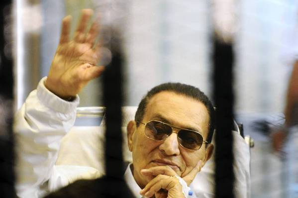 Former Egyptian President Hosni Mubarak waves from behind bars at a court hearing last week.
