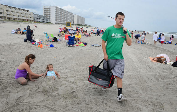 Kevin Bottomley, 17, of Sea Isle, N.J., walks to the beach near JFK Boulevard to make an on-beach food delivery for Drifters Feel Good Food take-out restaurant of Sea Isle City.