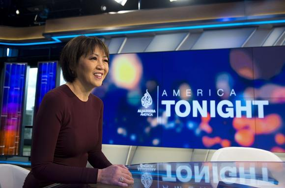 A photo of Joie Chen, smiling, with the America Tonight logo on a screen behind her. She's sitting at a anchor desk with a shiny top, brightly light, waiting to deliver the news.