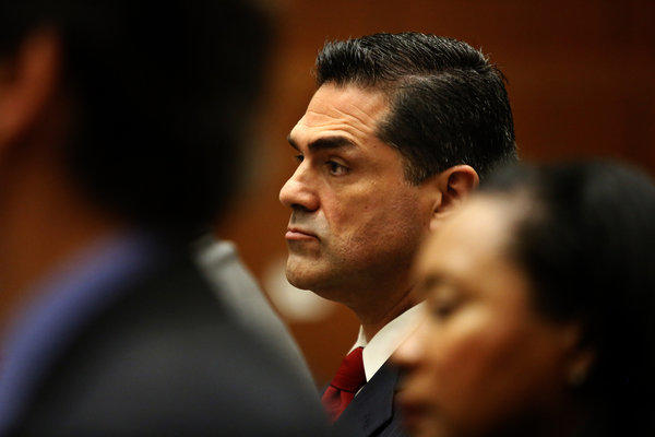 L.A. County Assessor John Noguez, center, has been out on paid leave to prepare his defense.