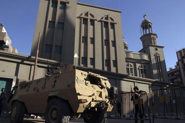 An Egyptian armored vehicle and army soldiers stand guard outside the main Christian Orthodox Cathedral in the southern city of Assiut, Egypt.