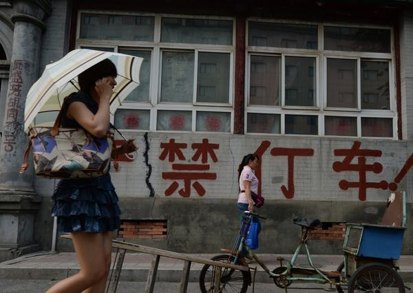 A Chinese woman walks past an old house in Beijing.