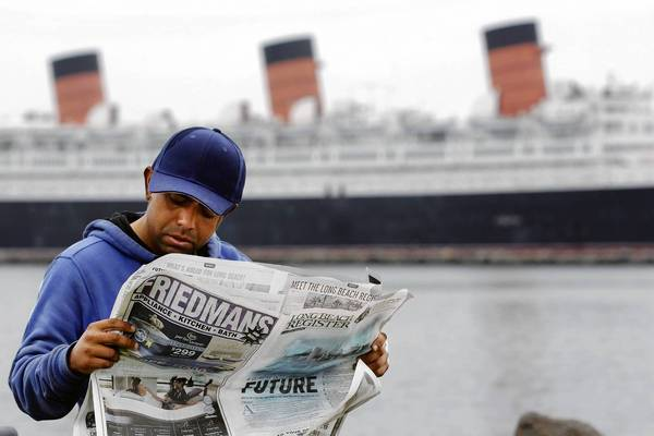 Long Beach resident Antonio Romero reads the inaugural edition of the Long Beach Register in front of the Queen Mary. The newspaper will be published five days a week and will compete against the Long Beach Press-Telegram.