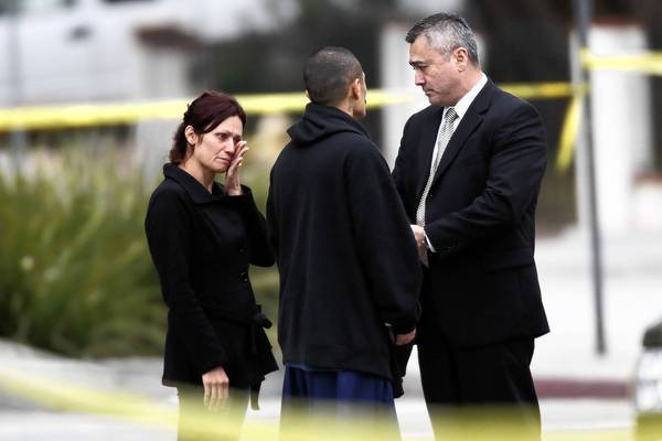 Parents, left, of a shooting victim talk to a Pomona police investigator near the crime scene in the 300 block of Orchid Lane.