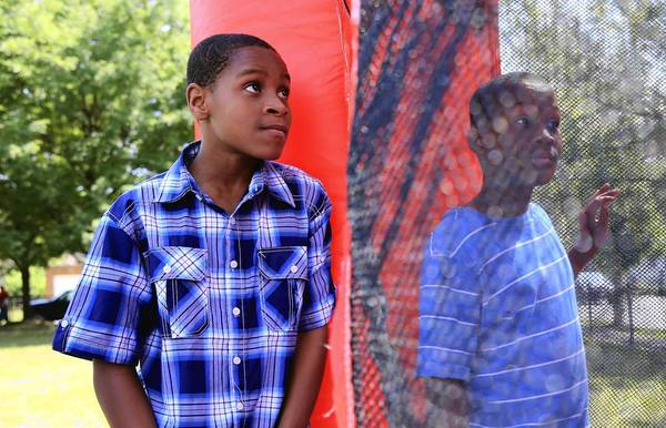 Cadavious Barrett, 13, waits his turn at an inflatable bounce house at a back-to-school event Friday at Haley Elementary Academy in Chicago. Haley will be taking in students from West Pullman Elementary, which closed in June. Cadavious attended West Pullman.