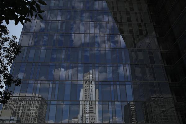 Los Angeles City Hall is reflected in the glass of the LAPD headquarters building downtown.