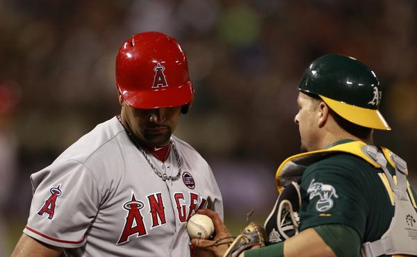 Angels slugger Albert Pujols, left, is tagged out by Oakland Athletics catcher Stephen Vogt during a game in July. Pujols will miss the rest of the season because of a lingering foot injury.