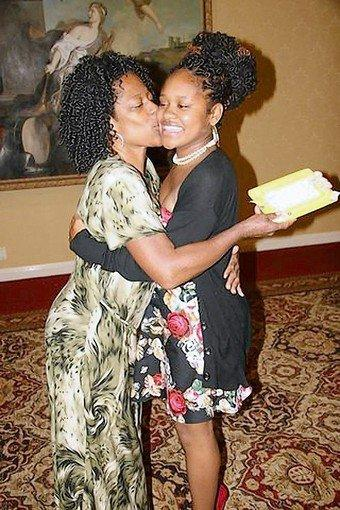 Tracie Smith, left, hugs her daughter DeJanee Smith, a student who received a college scholarship from Neighborhood Youth Achievers.