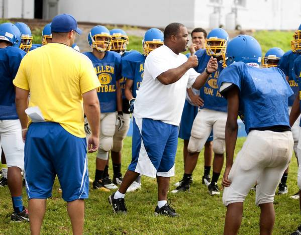 Allen High School Head Football Coach George Clay goes over some block shedding tips with his team at practice on Monday.