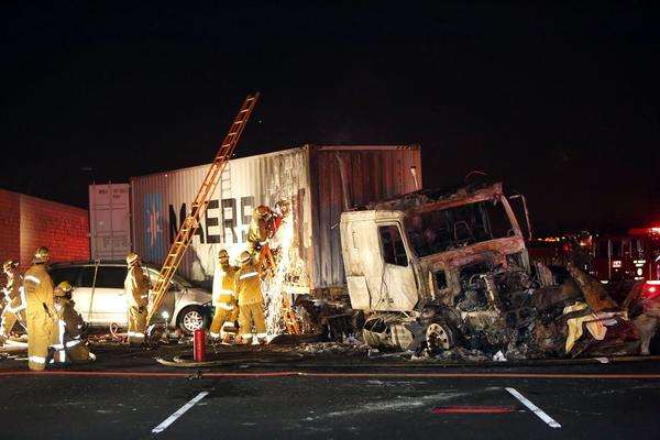 Firefighters work the scene iof a deadly big rig crash on the 10 Freeway in Pomona that shut down lanes in all directions Monday night.