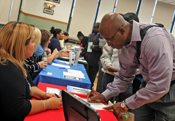 A job seeker fills out an application at an Illinois Department of Employment Security (IDES) job fair in Chicago.