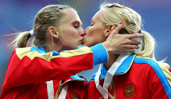Russian sprinters Kseniya Ryzhova and Yulia Guashcina share a kiss on the victory stand after their team won the 400-meter relay at the track and field world championships in Moscow over the weekend.