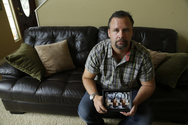 Retired U.S. Army Staff Sgt. Shawn Manning, at his home in Lacey, Wash., holds a photograph from a memorial for victims of a 2009 mass shooting at Ft. Hood, Texas. Manning, who still carries two bullets in his body from the shooting that killed 13 people, testified against Maj. Nidal Malik Hasan, the accused shooter.