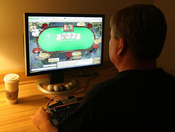 A Manassas, Va., man plays poker on his computer connected to an Internet gaming site.