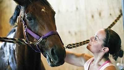 Terri Delucca, of Canton, pets a horse after her riding lesson at Touch of Class Riding School in Aberdeen on Tuesday afternoon.