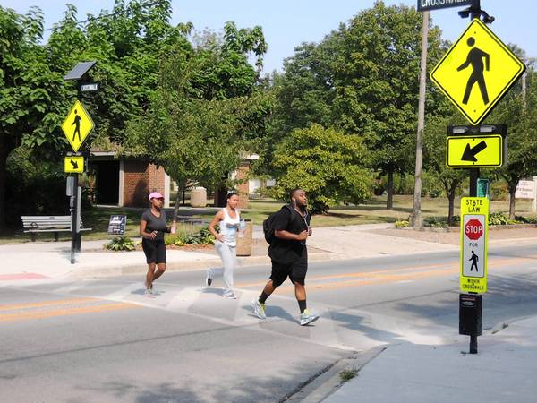Prairie Path runners cross York Street at the site of a possible future underpass for pedestrians and bicyclists.